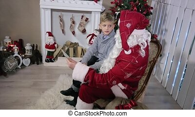 Santa and Little Boy Talk About Gifts with Tablet on Hand