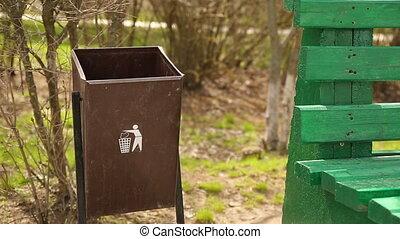 Garbage in a Trash Bin - Woman drops garbage in a trash bin