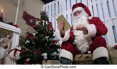 Santa Turns Page on Digital Tablet Buy and Pay Gifts.
