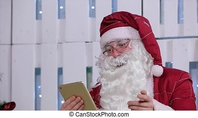 Santa Claus Flipping Page on Digital Tablet in Room with Christmas Tree and Gifts