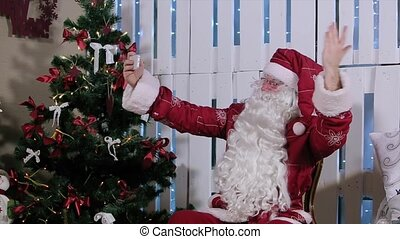 Santa Claus Is Sit and Make Selfi His Smartphone, Room with Fireplace and Christmas Tree, Gifts.