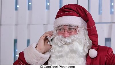Santa Claus Talking His Smatrphone in Room with Christmas Tree and Gifts
