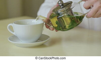 woman pours green tea from teapot HD