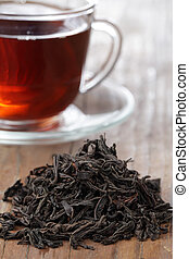 Black tea - Heap of dried tea leaves and a cup of black tea