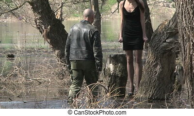 Man With Woman On Shoulders Walking In Flooded Grove