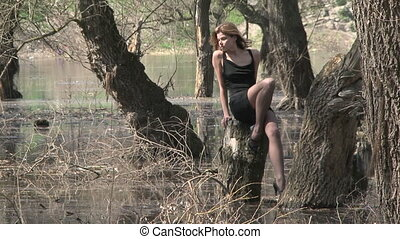 Gorgeous Female Model Sitting On Stump At Flooded Park