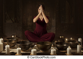 Tibetan singing bowls - Young woman meditates before playing...