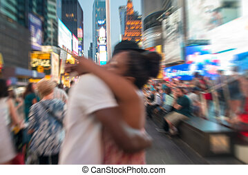 Blurred view of couple embracing at Times Square, New York City