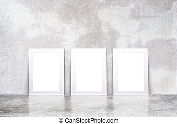 Blank white picture frames in empty loft room with concrete floor and wall, mock up