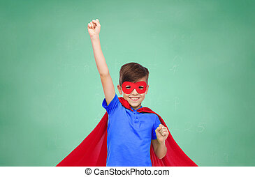 boy in red superhero cape and mask showing fists -...