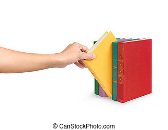 a female hand picks a book from the bright stack of vintage...