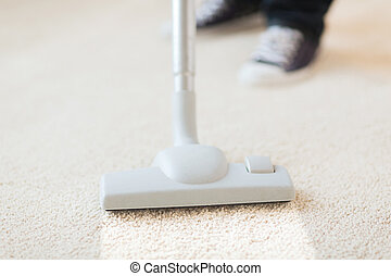 close up of male hoovering carpet - cleaning and home...