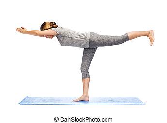 woman making yoga warrior pose on mat