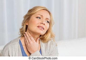 unhappy woman suffering from throat pain at home - people,...