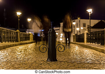 Night street with passers in Tavira. Portugal