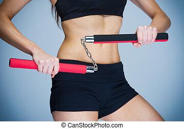 mujer, entrenamiento, con, nunchaku,