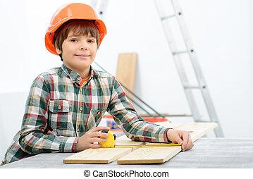 Positive boy holding tape measure - Little builder Pleasant...