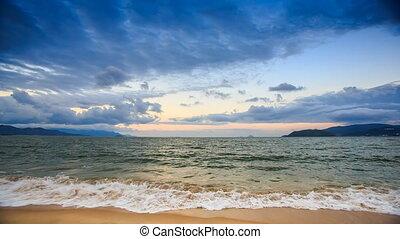 Foamy Sea Surf on Sand Beach Cloudy Sky at Sunset