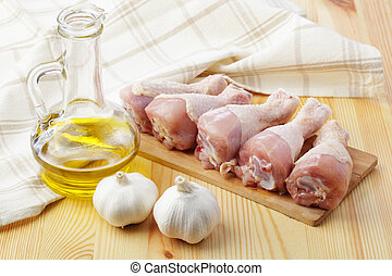 Raw chicken legs on a wooden board with garlic and olive oil