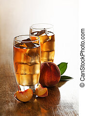 Ice tea - Glass of peach ice tea with slices cubes.