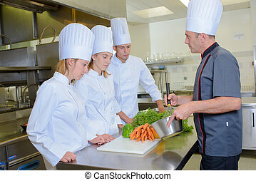 Chef whisking ingredients in front of students
