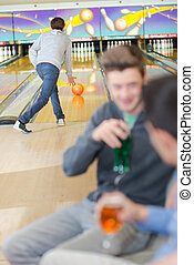 Man bowling while friends have a drink