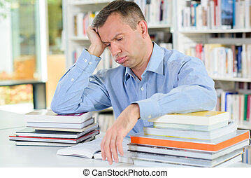 Tired man with stack of books