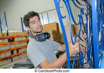 Man holding metal gate