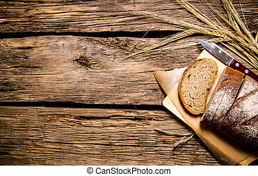Fresh bread with ears of rye. On wooden table.
