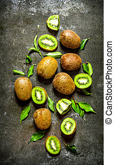 Kiwi with leaves . On the stone table .