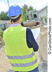 Surveyor looking at building site
