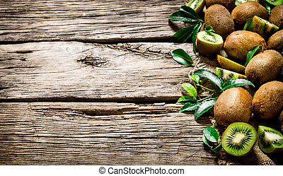 Fresh kiwi with leaves. On wooden background.