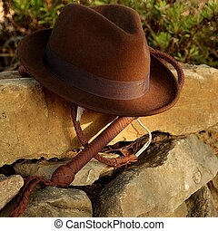 Fedora hat and bullwhip on a stone wall Indiana Jones theme