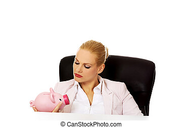 Angry business woman looking for her piggybank and sitting...