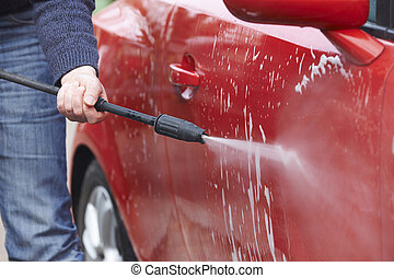 Man Washing Car With Pressure Washer