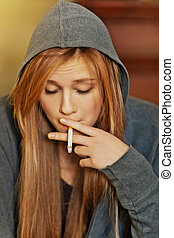 Teenage woman sitting on stairscase and smoking cigarette.