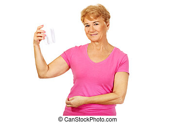 Smiling senior woman holding a tooth model.