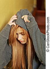 Teenage depressed woman sitting on stairscase.