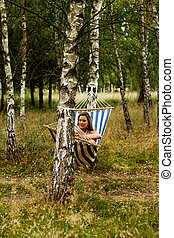 Young woman on hammock holding a mobile phone