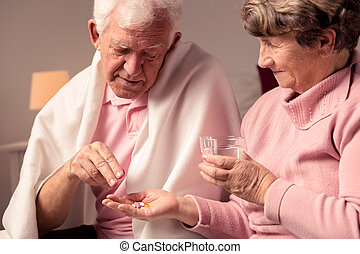 Wife giving medicines to husband