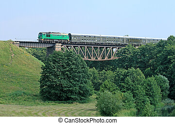 Passenger train passing through the big steel bridge