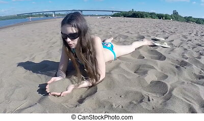 Attractive young girl is lying on a beach.