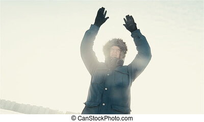 Hiker cheering elated and blissful with arms raised in the sky