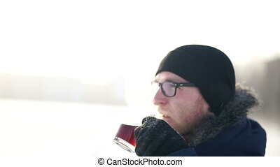 young man drinking hot coffee outdoors in cold winter day