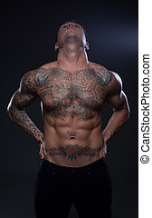 shirtless tattoed man with sixpack looking fit