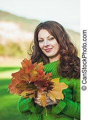 Beautiful woman with  autumnal maple leaves