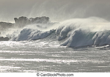 Stormy waves against dangerous cliff at noon