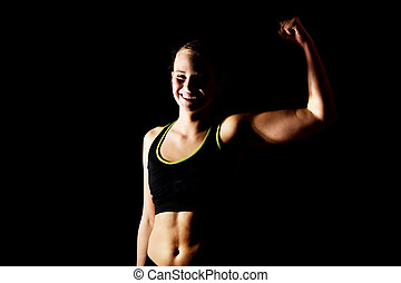 Young athletic woman shows her muscles