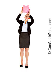 Young business woman shaking a piggybank.