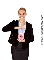 Young business woman protects piggybank